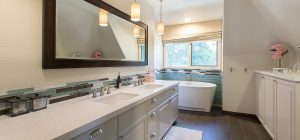 A newly remodeled bathroom with a long, beautiful sink, a bath tub, and some cabinets for storage.